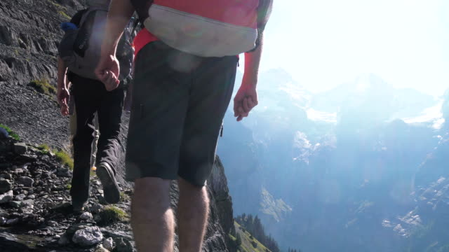 group of hikers ascend steep mountain slope above lake - t shirt stock-videos und b-roll-filmmaterial