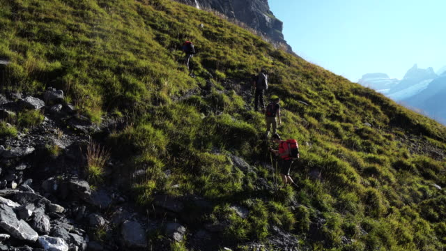 group of hikers ascend steep mountain slope above lake - freizeitaktivität stock-videos und b-roll-filmmaterial
