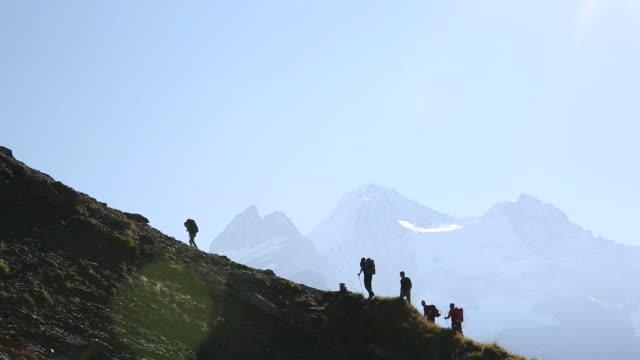vídeos de stock, filmes e b-roll de group of hikers ascends steep mountain ridge crest - amizade masculina
