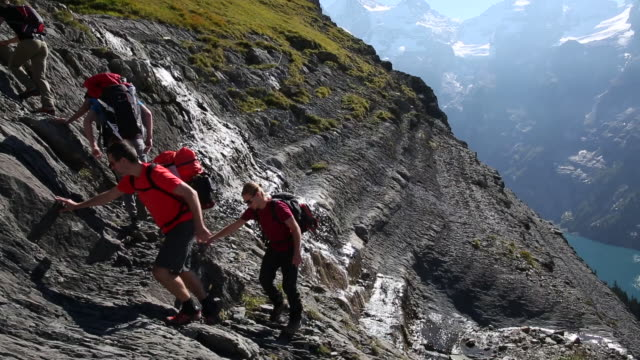 group of hikers ascends steep mountain slope above lake - t shirt stock-videos und b-roll-filmmaterial