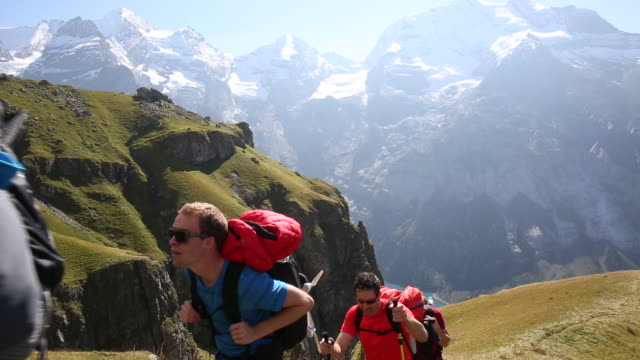 group of hikers ascends steep mountain slope above lake - maglietta video stock e b–roll