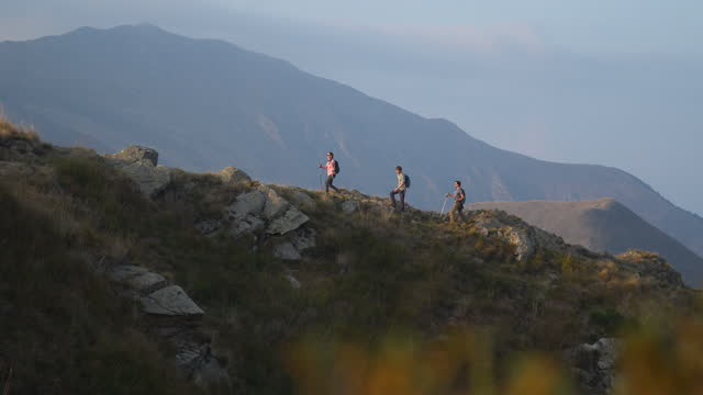 group of hikers hiking along a mountain ridge at sunset - climbing equipment stock videos & royalty-free footage