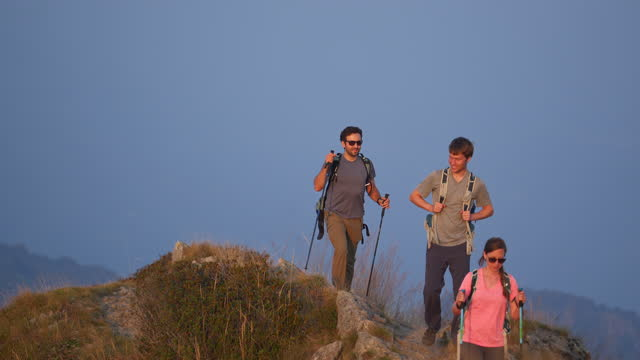 group of hikers hiking along a mountain ridge at sunset - fade out video transition stock videos & royalty-free footage