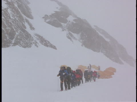 A group of hikers trudge away from camp in blowing snow.