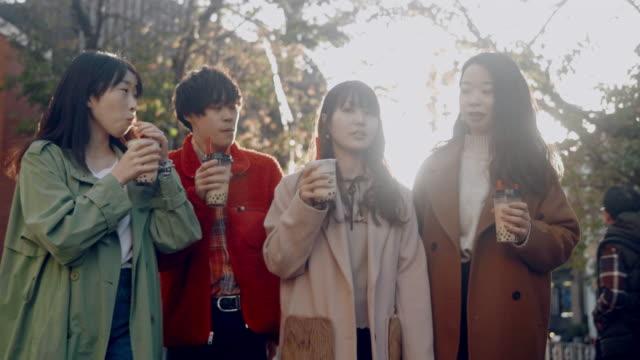 原宿でぶらぶらしている日本人の股関節の若い成人のグループ - ティーンエイジャー点の映像素材/bロール