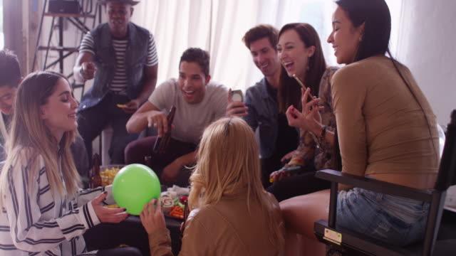 vídeos y material grabado en eventos de stock de group of hip young friends blowing up balloons for party while having fun and smiling - helio