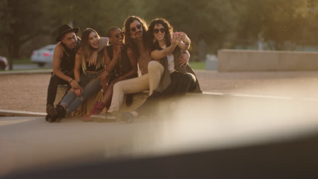 vídeos de stock e filmes b-roll de group of hip young friends pose for smartphone selfie while sitting on city street corner waiting for ride to music festival. - diversidade
