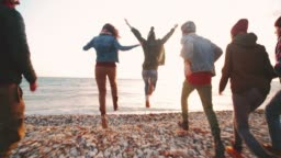 Group of hipsters jumping on the beach and having fun