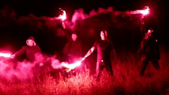 vidéos et rushes de groupe de hooligans tenant des torches dans la nuit - smoke physical structure