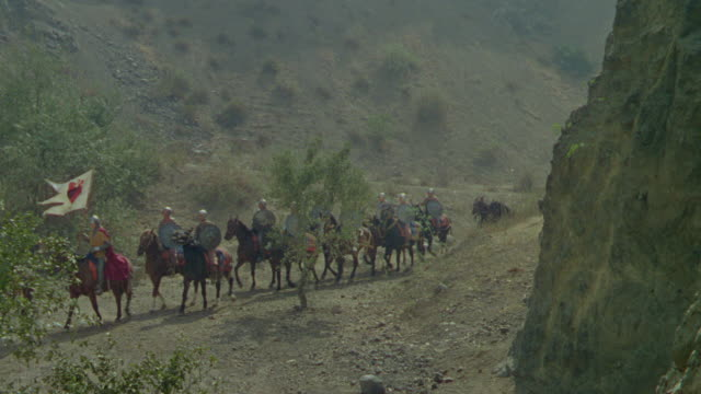 WS Group of horsemen pulling wagons on trail through rural area