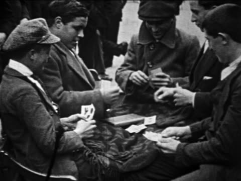 b/w 1913 group of immigrant men sitting outdoors playing card game / newsreel - 1913 stock-videos und b-roll-filmmaterial