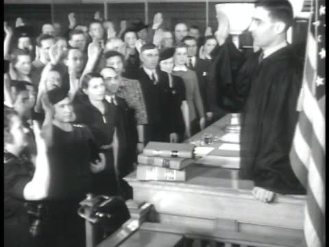 vídeos de stock e filmes b-roll de group of immigrant people w/ right hands raised, standing before judge, sot administering oath of citizenship: 'do you solemnly swear...you will... - cidadão