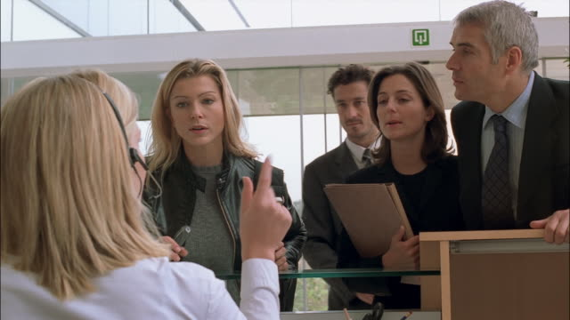 a group of impatient businessmen and businesswomen talk to a receptionist in an office lobby. - 受付係点の映像素材/bロール
