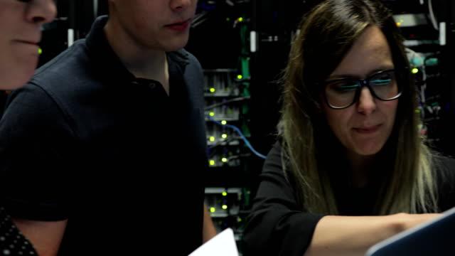Group of IT Engineers Working in Server Room