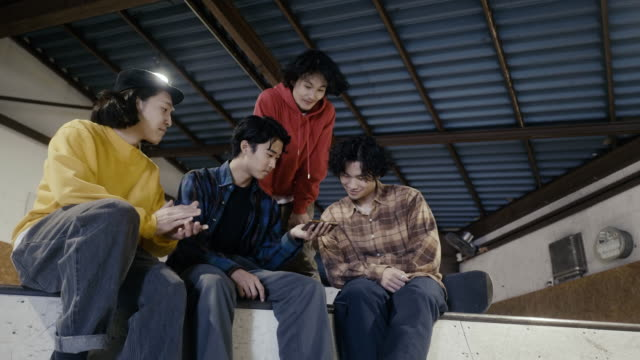 group of japanese boys watching skateboarding video on smart phone - small group of people stock videos & royalty-free footage