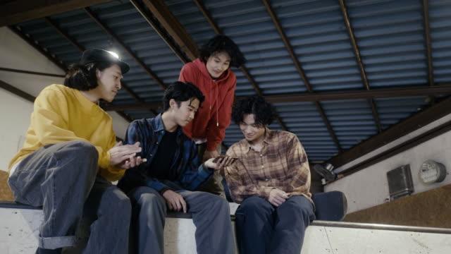 gruppe von japanischen jungs beobachten skateboarding-video auf dem smartphone - kleine personengruppe stock-videos und b-roll-filmmaterial