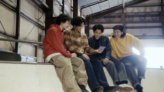 vídeos y material grabado en eventos de stock de grupo de chicos japoneses viendo video en el teléfono inteligente - cuatro personas
