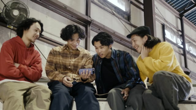 group of japanese boys watching video on smart phone (slow motion) - only japanese stock videos & royalty-free footage