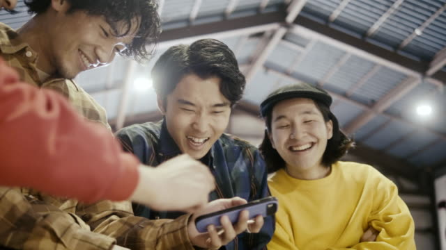 vídeos de stock e filmes b-roll de group of japanese boys watching video on smart phone (slow motion) - cultura jovem