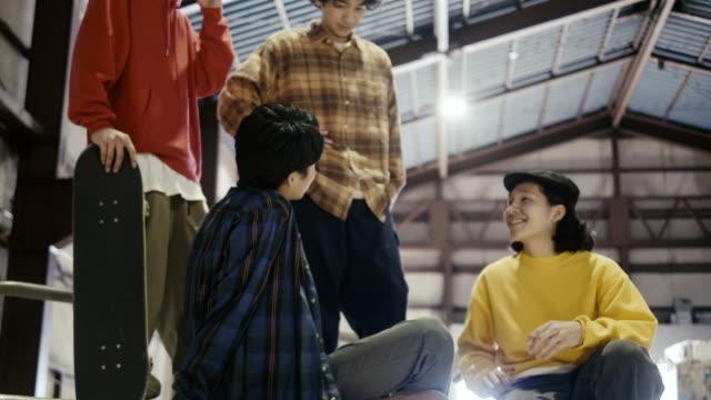 stockvideo's en b-roll-footage met groep japanse skateboardervrienden die tijd samen in het skatepark doorbrengen - skateboardpark