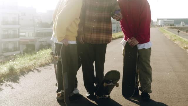 vídeos de stock, filmes e b-roll de grupo de skatistas japoneses usando telefone inteligente (câmera lenta) - meninos adolescentes