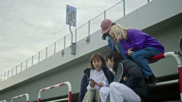 スマートフォンでビデオを見ている日本のスケートボーダーのグループ - 文化点の映像素材/bロール