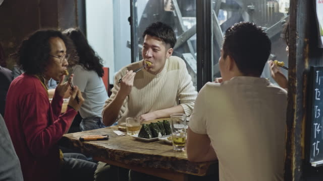 group of japanese young people enjoying dinner at tokyo restaurant - sushi video stock e b–roll