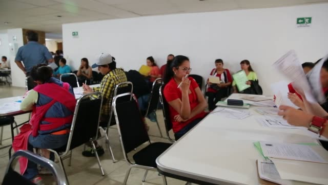 vídeos de stock, filmes e b-roll de a group of job searchers fill out applications for admission for unemployment insurance cards in mexico city mexico a woman hands a completed... - méxico central