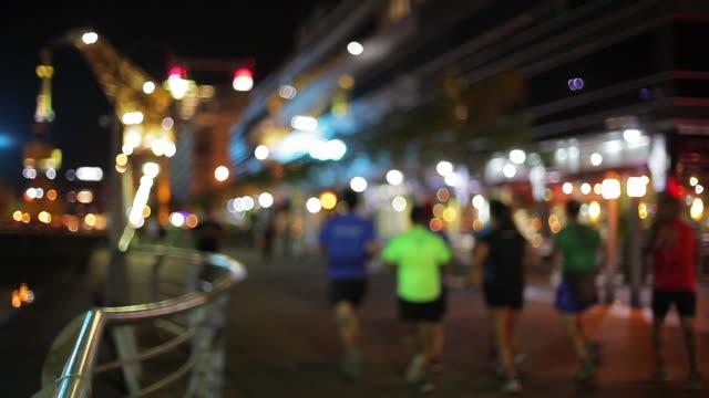 group of joggers on city street at night defocused - プエルトマデロ点の映像素材/bロール