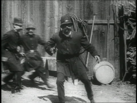 b/w 1914 group of keystone kops arriving on scene + looking around / feature - 1914 stock videos & royalty-free footage