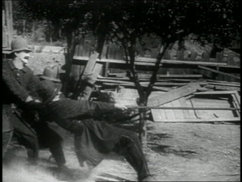 vídeos de stock, filmes e b-roll de b/w 1914 group of keystone kops being pulled by rope falling down / feature - puxando