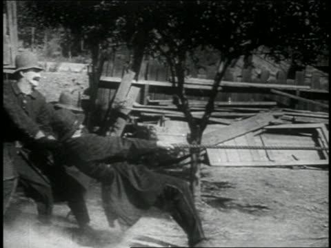 b/w 1914 group of keystone kops being pulled by rope falling down / feature - dra bildbanksvideor och videomaterial från bakom kulisserna