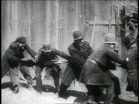 b/w 1914 group of keystone kops being pulled by rope / feature - 1914年点の映像素材/bロール