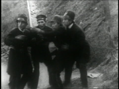 b/w 1916 group of keystone kops pointing at something + running offscreen / feature - 1916 stock videos & royalty-free footage
