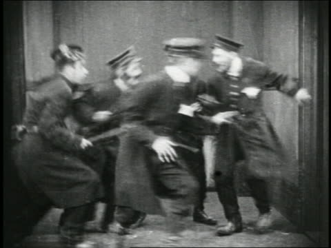 stockvideo's en b-roll-footage met b/w 1915 group of keystone kops running + bumping around small room + running up stairs / fetaure - 1915