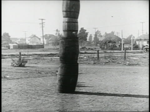 b/w 1924 group of keystone kops running into stack of barrels / police truck driving from barrels - 1924 stock-videos und b-roll-filmmaterial