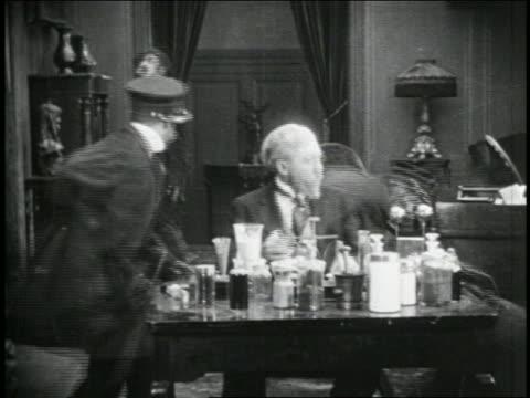 b/w 1915 group of keystone kops searching room where senior man is trying to work at desk - 1915年点の映像素材/bロール