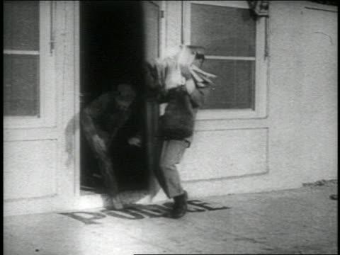 b/w 1914 group of keystone kops smacking into postman walking past doorway + falling down - postal worker stock videos and b-roll footage