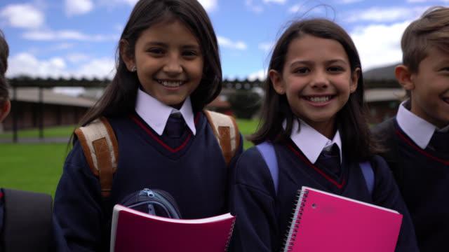 ノートを持ち、カメラに向かって笑顔を見せている学校の子供たちのグループ - 初登校日点の映像素材/bロール