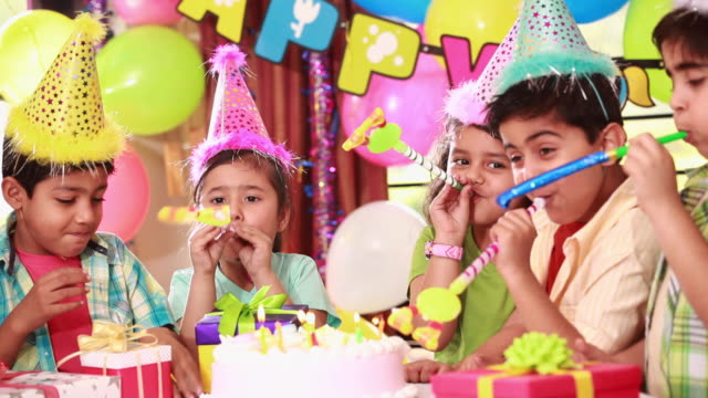 vídeos de stock, filmes e b-roll de group of kids blowing party blow horn in birthday celebration  - aniversário