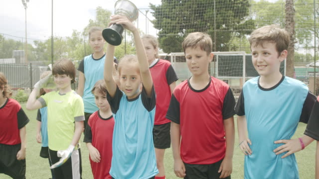 group of kids celebrating together the winning of a competition running on a soccer field - soccer competition stock videos & royalty-free footage