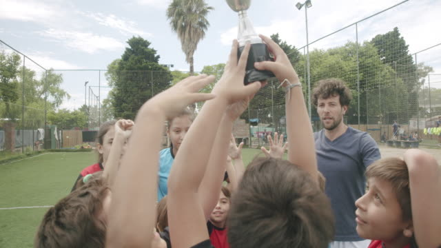 group of kids celebrating together the winning of a competition on a soccer field - soccer competition stock videos & royalty-free footage
