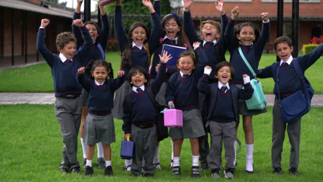 group of kids celebrating while smiling at camera at school - first day of school stock videos & royalty-free footage