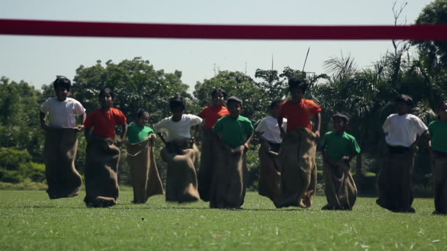 group of kids doing sack race in the park  - sack race stock videos & royalty-free footage