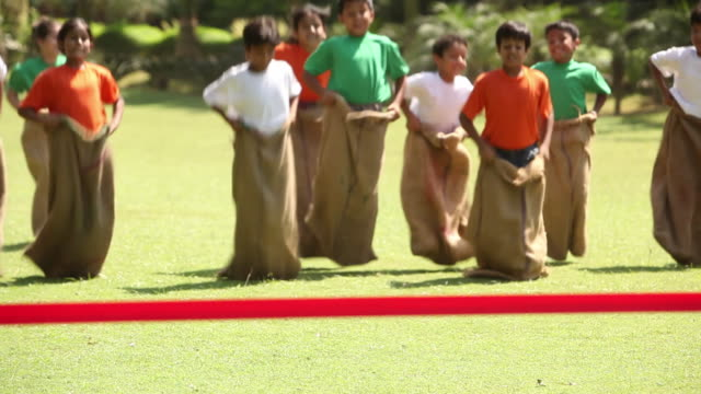 group of kids doing sack race in the park  - sack stock-videos und b-roll-filmmaterial