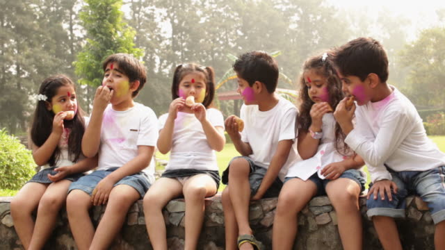 vídeos de stock e filmes b-roll de group of kids eating gujia in holi festivals - lanche