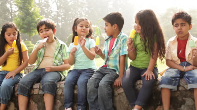 group of kids eating ice cream in a park  - ledge stock videos & royalty-free footage