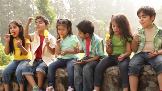 Group of kids eating ice cream in a park