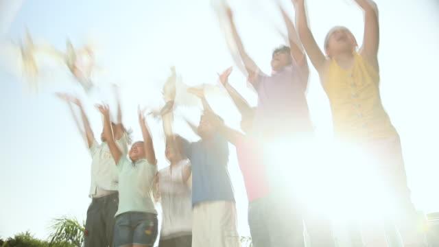 vídeos de stock, filmes e b-roll de group of kids flying pigeon  - somente crianças
