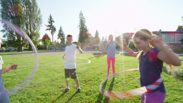 ms slo mo group of kids hula hooping on grass field in front of school - playground stock videos & royalty-free footage